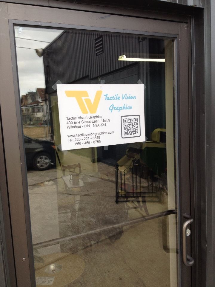 The outer office door with a sign that reads Tactile Vision Graphics Inc., 400 Erie Street East, Unit 9, Windsor ON N9A 3X4, 226-221-8849, 866-465-0755 and a QR code to our website